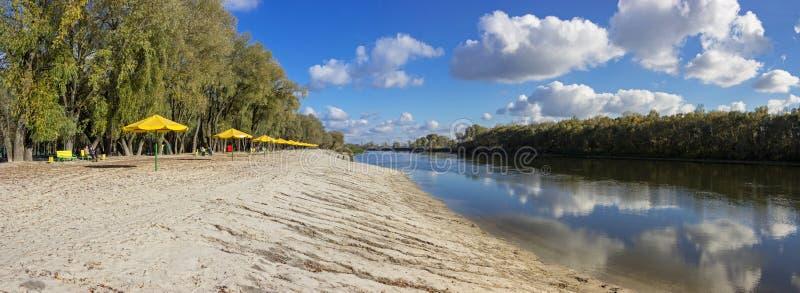 Paisagem bonita com reflexão no céu e nas nuvens do rio Guarda-chuvas amarelos na praia imagem de stock