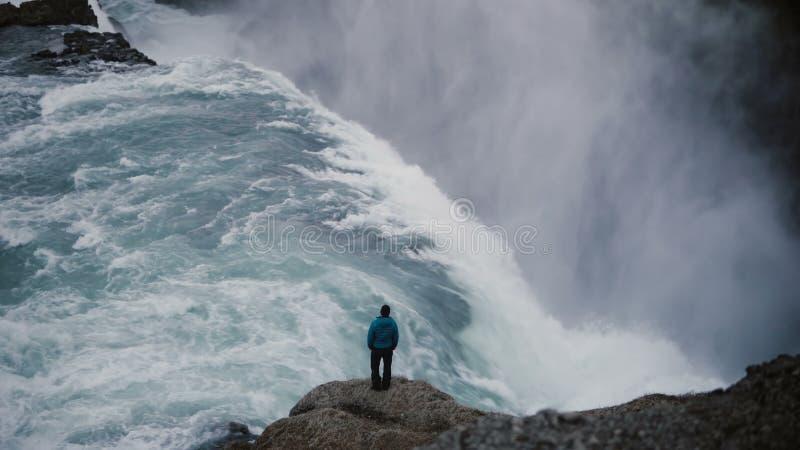 Paisagem bonita da cachoeira de Gullfoss Opinião traseira o homem que está na borda da rocha e que aprecia a vista imagens de stock royalty free