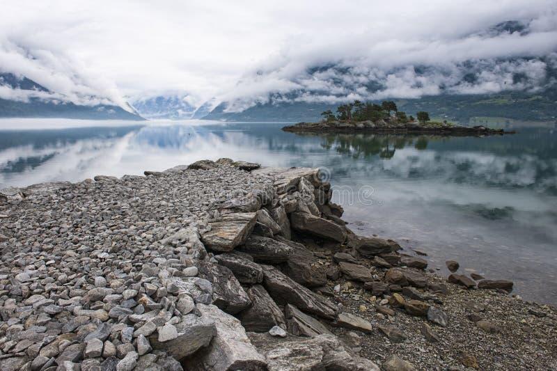 Paisagem bonita da manhã no fiorde Cais de pedra e ilha rochosa com árvores e nuvens do rastejamento, Noruega imagens de stock