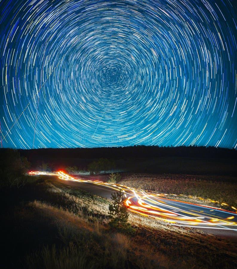 Paisagem bonita da noite, trilhas da estrela e trilhas do carro imagens de stock