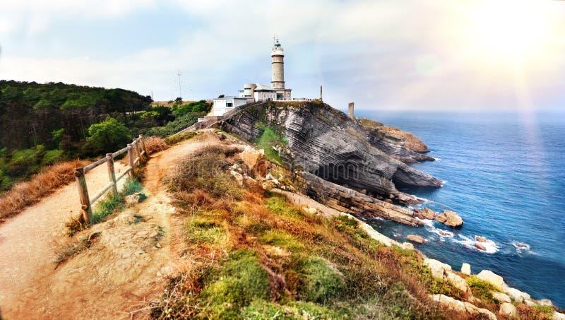 Paisagem bonita da praia e da costa com montanhas e vegetação Penhascos em Cantábria, prefeito Lighthouse de Cabo em Santander, t foto de stock