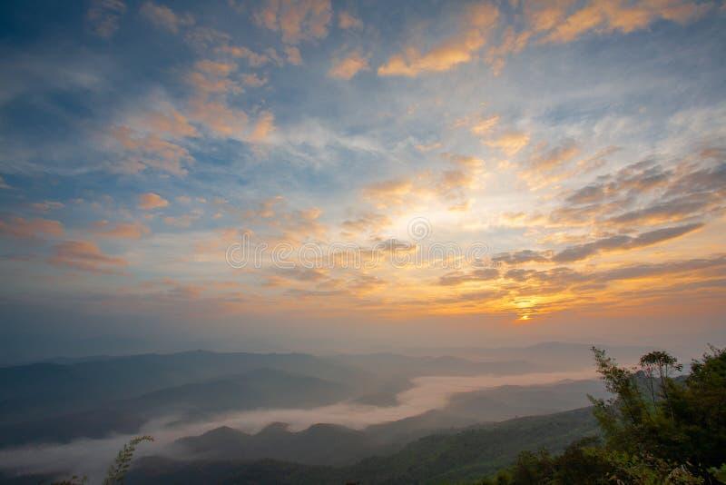 A paisagem bonita das montanhas na manhã, o sol é luz solar de aumentação e névoa no inverno em Doi Samer Dao, Nan, imagem de stock royalty free