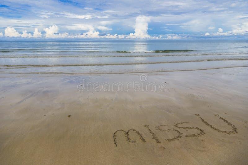 A paisagem bonita do mar e do branco do céu azul acena na praia com ` da senhorita U do ` das palavras no ` branco da praia da ar fotografia de stock
