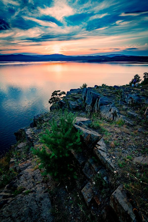Paisagem bonita do por do sol no lago da montanha com o sol que esconde atrás das montanhas foto de stock royalty free