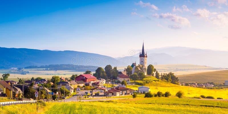 Paisagem bonita do vale nas montanhas de Eslováquia, casas pequenas na vila, cena rural Spissky Stvrtok, Eslováquia foto de stock