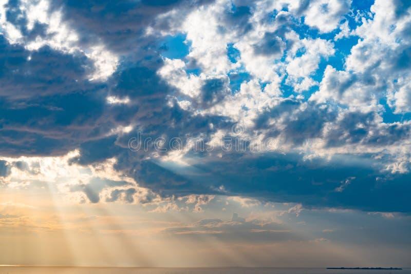 Paisagem bonita, os raios da explosão de nivelamento do sol através das nuvens imagens de stock