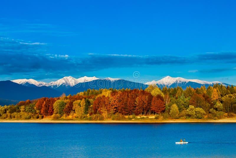 Paisagem colorida do outono com lago e um barco foto de stock royalty free