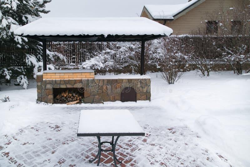Paisagem com área do assado, snowbanks da neve branca, pinheiros no jardim do país fotografia de stock