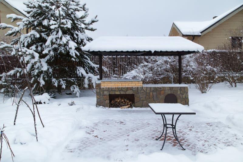 Paisagem com área do assado, snowbanks da neve branca, pinheiros no jardim do país imagem de stock