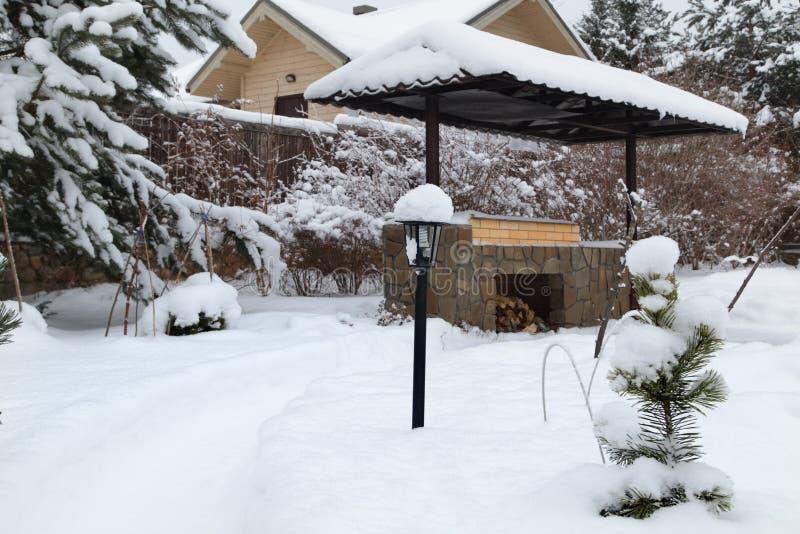 Paisagem com área do assado, snowbanks da neve branca, pinheiros no jardim do país foto de stock royalty free