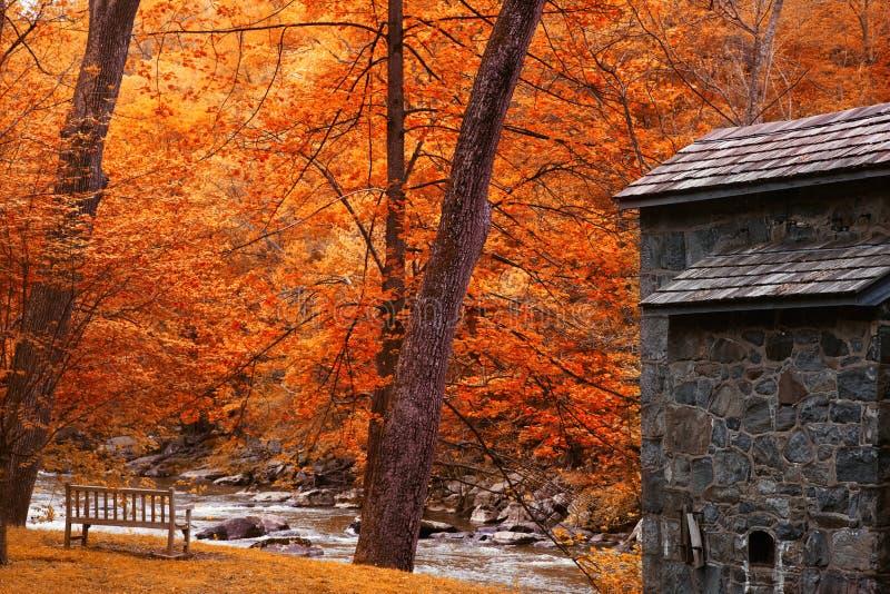 Paisagem com cabine, rio e árvores do outono imagens de stock