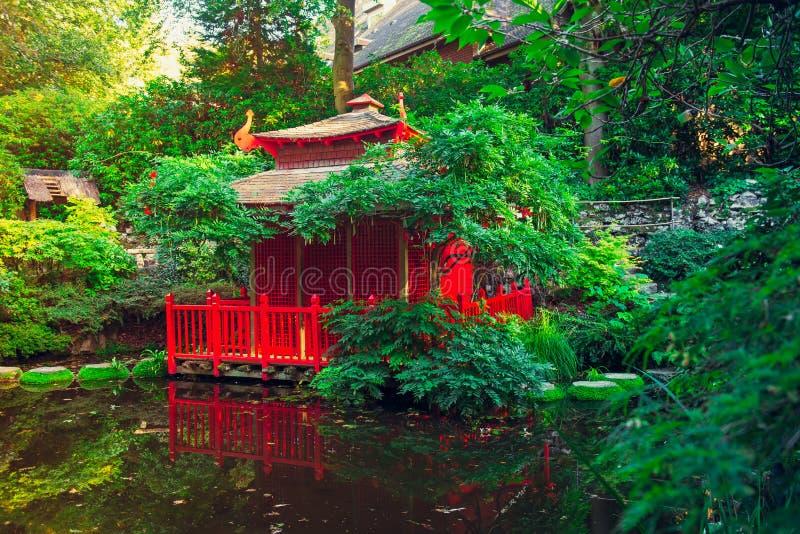 Paisagem com a casa de madeira vermelha no jardim bonito do estilo japonês, parque com lagoa Arquitetura tradicional de japão ext imagens de stock