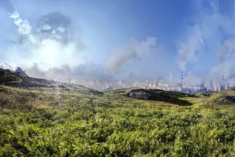 paisagem com grama verde com uma opinião da cidade no horizonte e na poluição perigosa foto de stock
