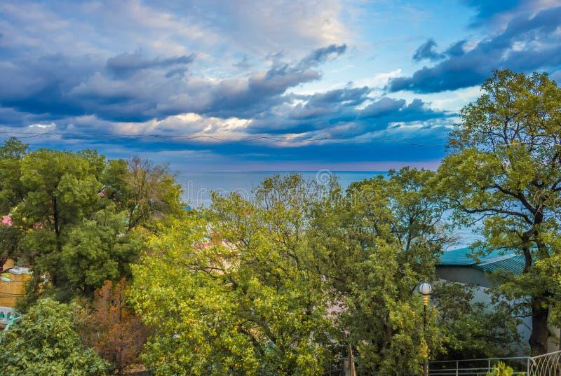 Paisagem com o céu nebuloso bonito, o mar e as árvores verdes luxúrias no verão imagem de stock royalty free