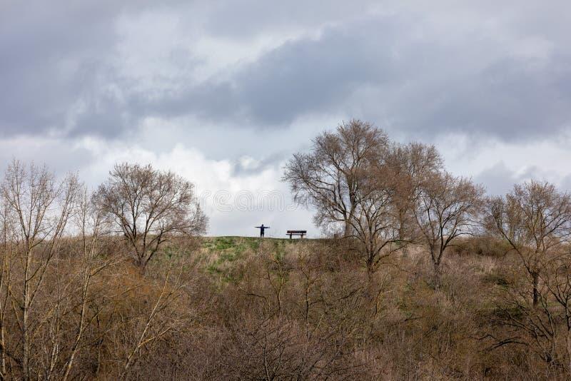 Paisagem com silhueta de um homem feliz ereto, braços aumentados-acima na montanha fotografia de stock