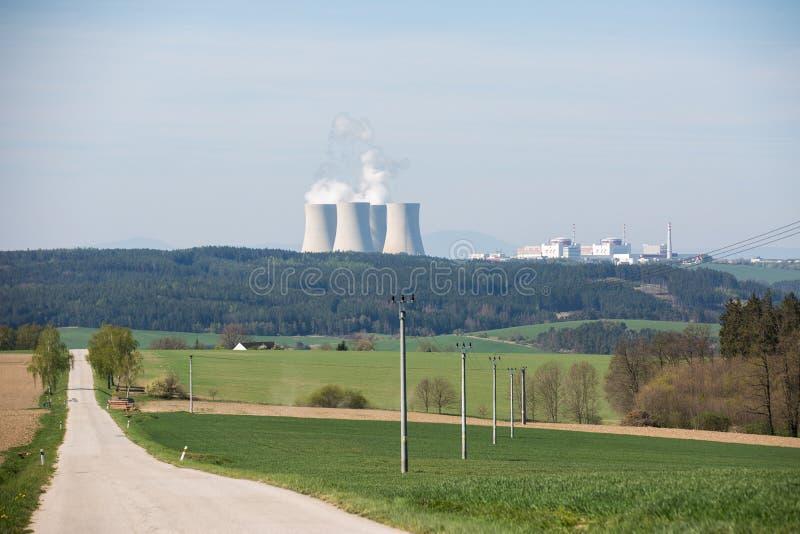 Paisagem com um central nuclear no horizonte imagens de stock