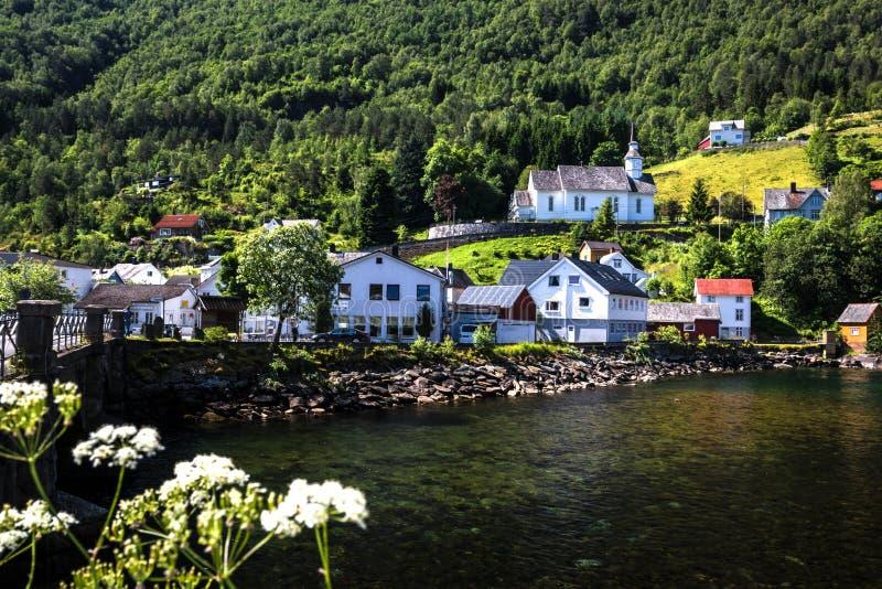 Paisagem com vista de uma vila norueguesa no meio das montanhas pelo fiorde de Geiranger no verão imagem de stock royalty free
