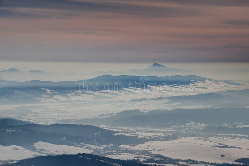 Paisagem congelada do inverno com os cumes da montanha sob o céu alaranjado imagem de stock royalty free