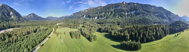 Paisagem cultural nos Alpes com prados e pastagens entre montanhas e colinas, panorama composto fotografia de stock royalty free