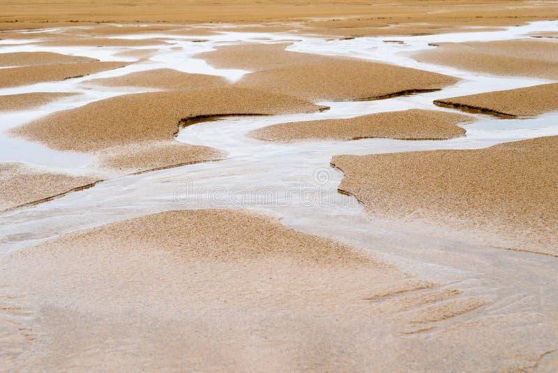 Paisagem da areia na maré baixa com sulcos da água fotos de stock royalty free