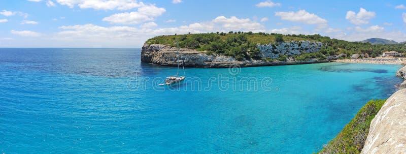 Paisagem da baía bonita do Mas do en do ` de Cala Estany d com um mar maravilhoso de turquesa, Cala Romantica, Porto Cristo, Majo imagem de stock