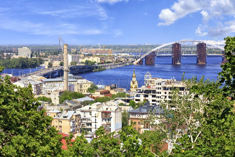 A paisagem da cidade do verão de Kiev com uma vista do rio de Dnieper, de muitas pontes e do distrito velho de Podol imagens de stock royalty free