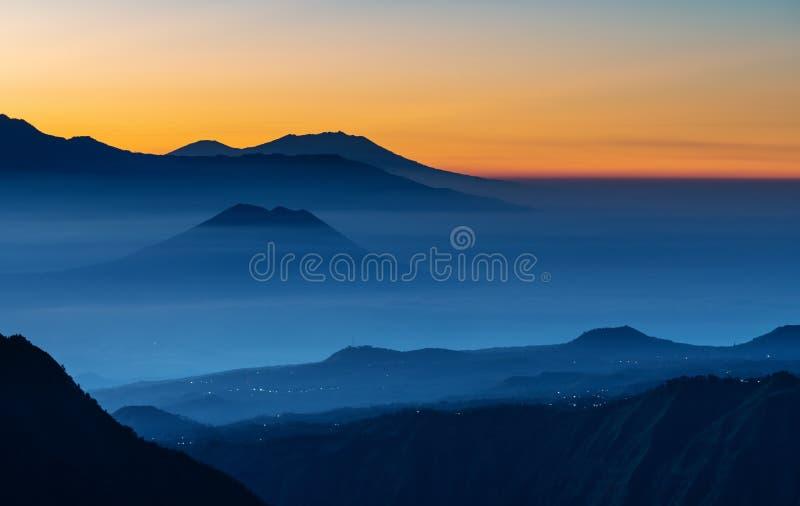 Paisagem da cordilheira e montanhas da silhueta com névoa colorida no nascer do sol imagem de stock royalty free