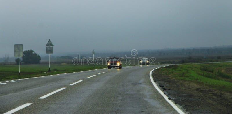 Paisagem da estrada com os carros moventes no dia fotografia de stock