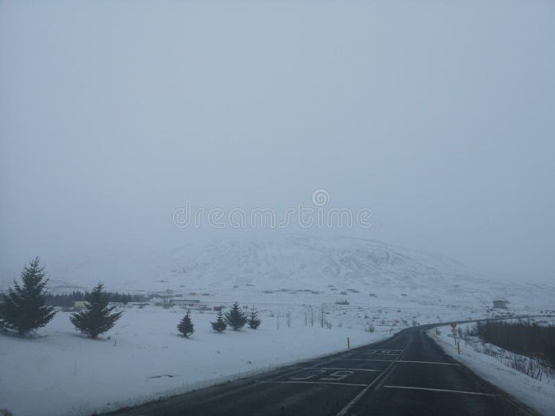 Paisagem da estrada do monte no inverno em Islândia Estrada asfaltada com lateralmente completamente da neve fotografia de stock