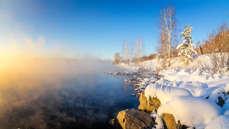 Paisagem da manhã da mola com névoa e uma floresta na costa de um lago, Rússia, os Ural, fevereiro imagens de stock royalty free