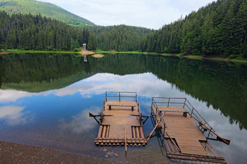 Paisagem da manhã do lago Synevyr da montanha com os dois flutuadores de madeira na costa Árvores altas velhas perto do lago foto de stock