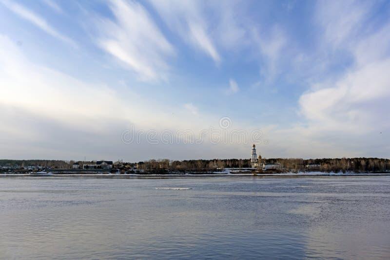 Paisagem da mola com uma banquisa de gelo que flutua no rio e em uma igreja ortodoxa no banco distante imagens de stock