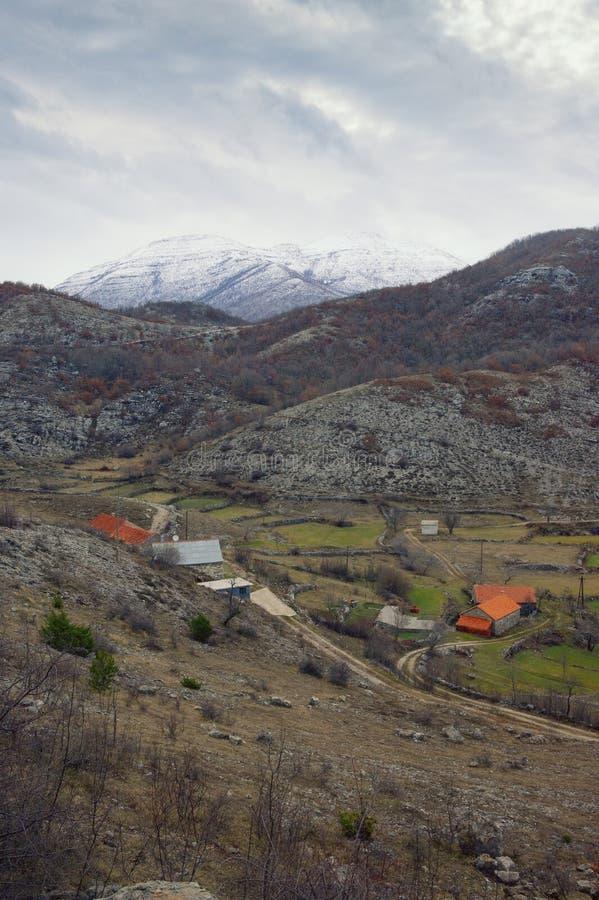 Paisagem da montanha com estrada secundária e a vila pequena no dia nebuloso Balcãs, Montenegro imagens de stock