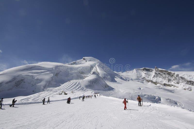 Paisagem da montanha com os esquiadores que esquiam afastado imagem de stock royalty free
