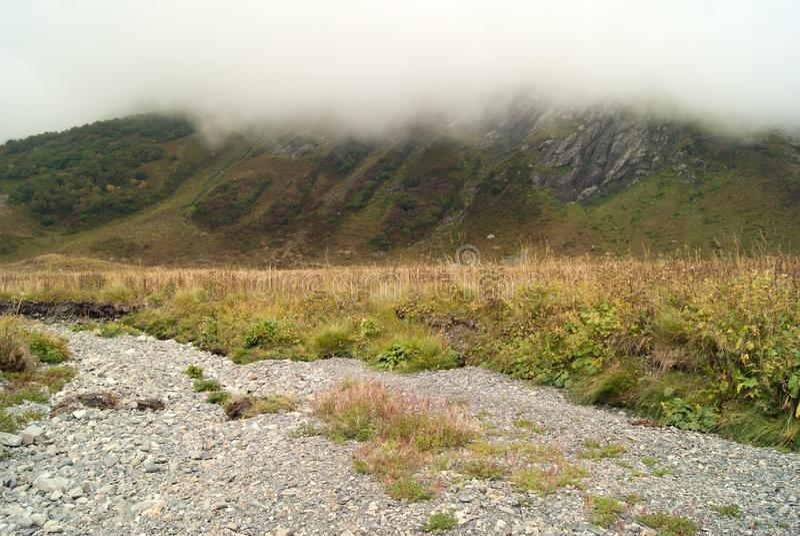 Paisagem da montanha com um canal seco e uma montanha escondidos por uma nuvem no fundo, imagem de stock royalty free