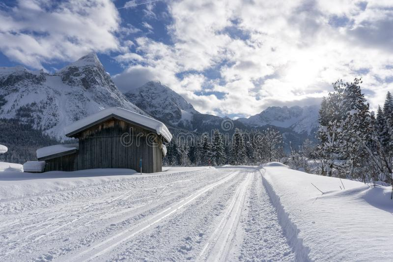 Paisagem da montanha do inverno com a trilha preparada do esqui e as árvores cobertos de neve ao longo da estrada foto de stock royalty free