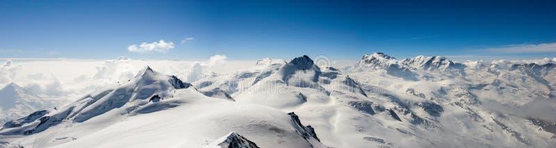 Paisagem da montanha do panorama nos cumes suíços perto de Zermatt em um dia bonito no inverno atrasado sob um céu azul imagem de stock royalty free