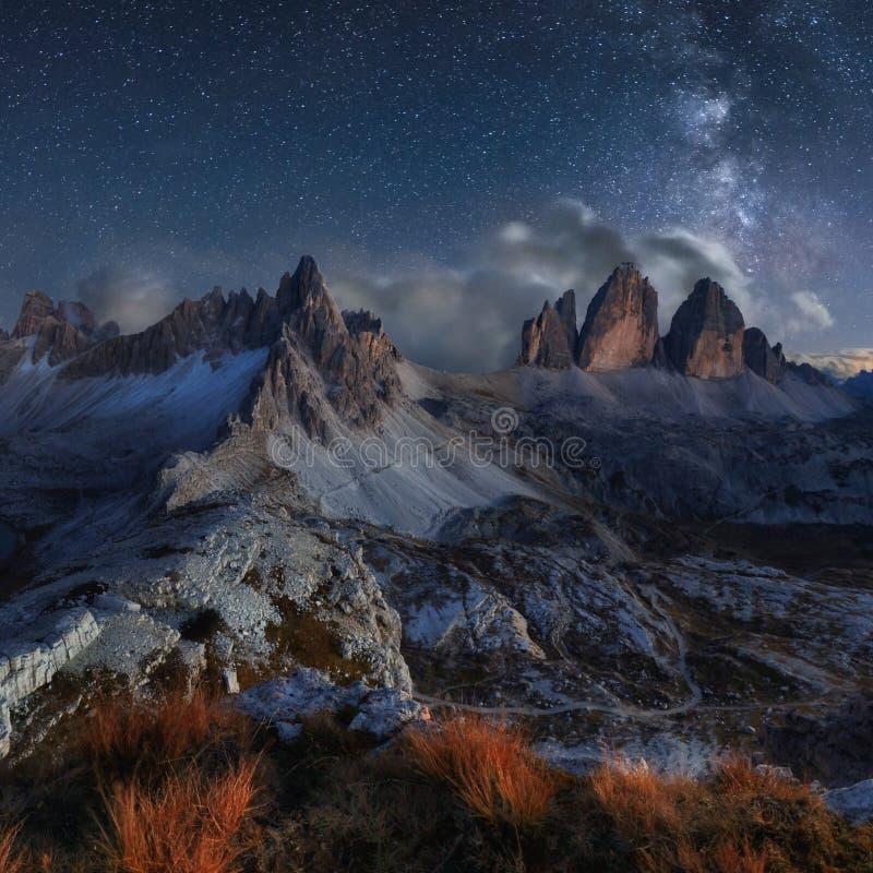 Paisagem da montanha dos cumes com céu noturno e maneira de Mliky, Tre Cime d imagens de stock