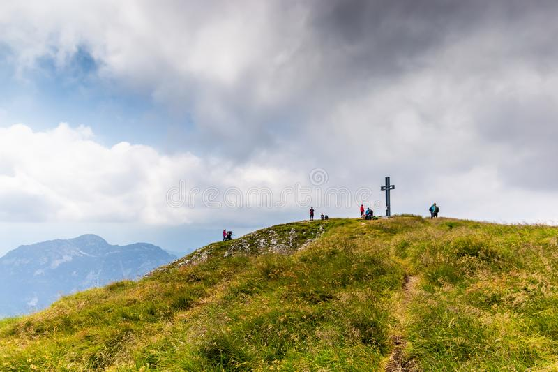 Paisagem da montanha em ?ustria Opinião a cruz e os turistas na parte superior do pico do vencido Alpes austr?acos fotos de stock royalty free