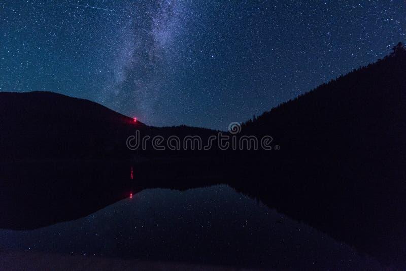 Paisagem da noite com céu estrelado e Via Látea durante o chuveiro de meteoro de Perseid sobre o lago alpino Synevyr em montanhas imagens de stock