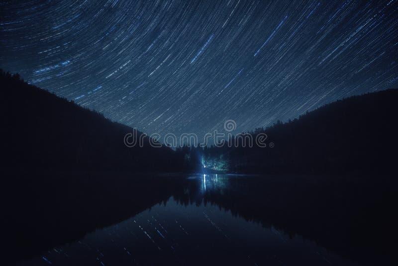 Paisagem da noite com céu estrelado, fugas da estrela sobre o lago alpino Synevyr em montanhas Carpathian fotografia de stock