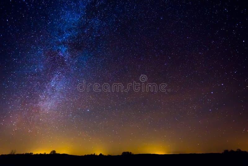 Paisagem da noite com Via Látea colorida e luz amarela no horizonte fotografia de stock