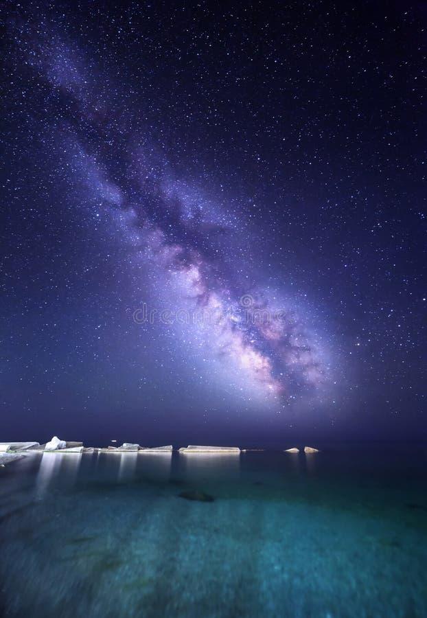 Paisagem da noite com Via Látea colorida no mar com pedras Céu estrelado Fundo do espaço imagem de stock