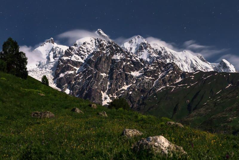 Paisagem da noite de montanhas rochosas com picos nevado em Svaneti, Geórgia Céu estrelado da noite e montanhas de Cáucaso imagens de stock royalty free