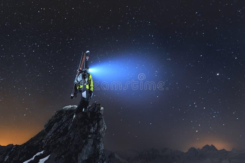 Paisagem da noite Um esquiador backcountry profissional com uma trouxa e os esquis está em uma rocha nas montanhas e brilha imagens de stock royalty free