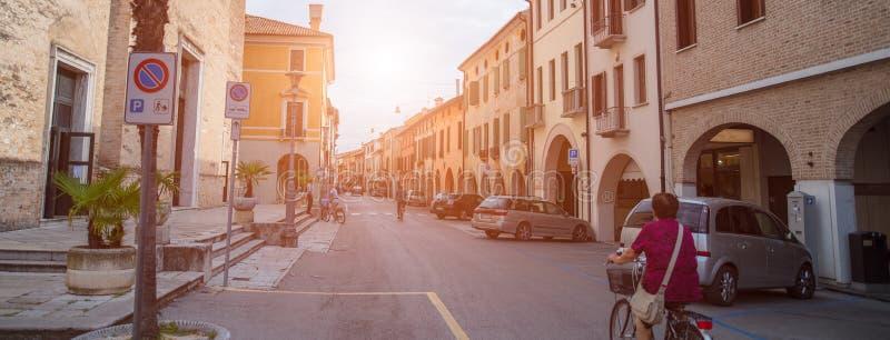 Paisagem da rua italiana, mulher adulta que monta uma bicicleta fotos de stock