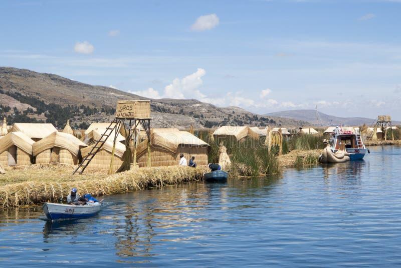 Paisagem das ilhas de flutuação de Uros nas cores azuis mágicas do lago Titicaca com a cordilheira de Andes dentro fotografia de stock royalty free