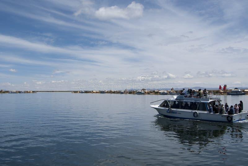 Paisagem das ilhas de flutuação de Uros nas cores azuis mágicas do lago Titicaca com a cordilheira de Andes dentro imagens de stock royalty free
