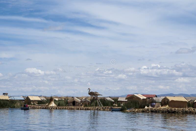 Paisagem das ilhas de flutuação de Uros nas cores azuis mágicas do lago Titicaca com a cordilheira de Andes dentro imagem de stock