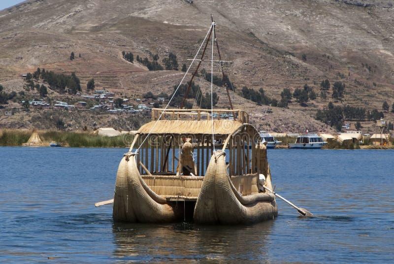 Paisagem das ilhas de flutuação de Uros nas cores azuis mágicas do lago Titicaca com a cordilheira de Andes dentro fotografia de stock